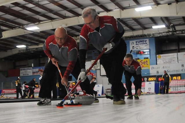 Northwest Territories third Brian Kelln and second Ben McDonald sweep lead Richard Klakowich's rock at the 2016 Canadian Seniors in Digby, N.S. (Curling Canada/Mike Lewis photo)