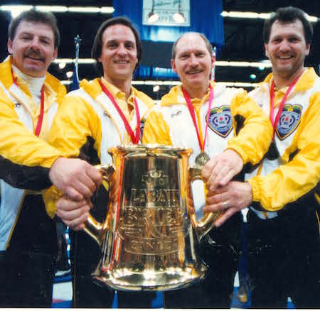 Vic Peters, left, and his teammates third Dan Carey, second Chris Neufeld and lead Don Rudd hoist the Labatt Tankard after winning the 1992 Brier. (Photo, Curling Canada/Michael Burns)