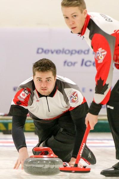Team Canada lead Rob Gordon prepares to sweep skip Matt Dunstone's rock during action against Switzerland at the 2016 World Junior Curling Championships (WCF/Richar Gray photo)