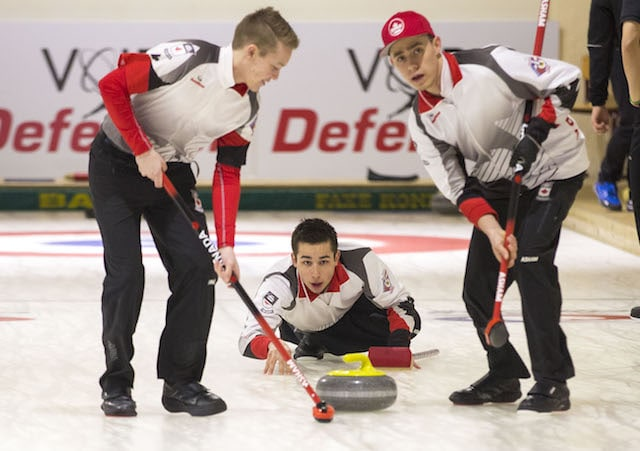 Team Canada third Colton Lott delivers his rock with sweepers Robbie Gordon and Kyle Doering watching closely (WCF/Marissa Tiel photo)