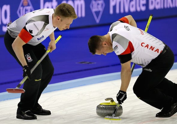 Team Canada's Ben Hebert, right, puts his back into it, with Marc Kennedy offering encouragement. (Photo, World Curling Federation/Richard Gray)