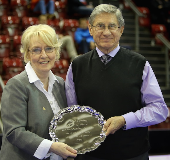 World Curling Federation president Kate Caithness, left, presents World Curling Hall of Fame plate to 2016 inductee Warren Hansen. (Photo, World Curling Federation/Richard Gray)