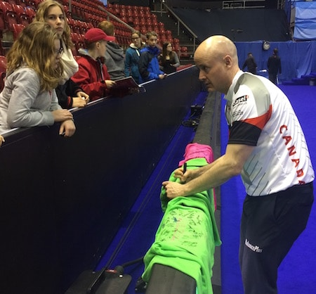 Team Canada skip Kevin Koe signs autographs for fans after Tuesday's win. (Photo, Curling Canada)