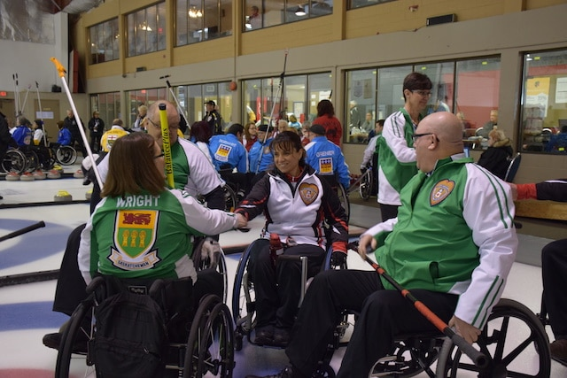 Teams Saskatchewan and Ontario shake hands after their game on the first day of competition at the 2016 Canadian Wheelchair Curling Championship at the Callie Curling Club in Regina (Curling Canada/Morgan Daw photo)