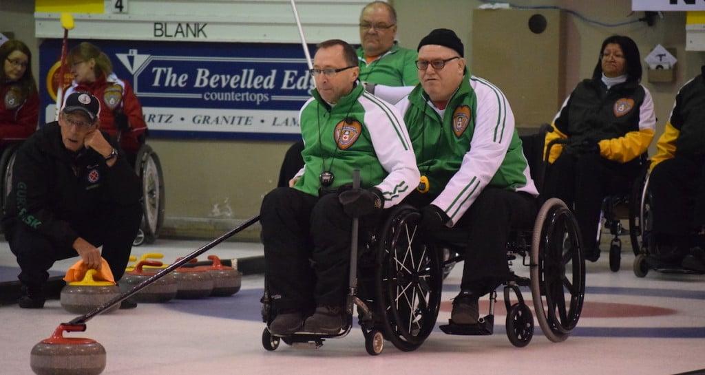 Saskatchewan skip Darwin Bender delivers his stone with help from teammate Lloyd Thiele at the 2016 Wheelchair Curling Championship in Regina (Curling Canada/Morgan Daw photo)
