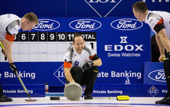 Brent Laing (in the hack) shares a laugh with teammates Marc Kennedy, left, and Ben Hebert during Wednesday's win. (Photo, World Curling Federation/Céline Stuckli)