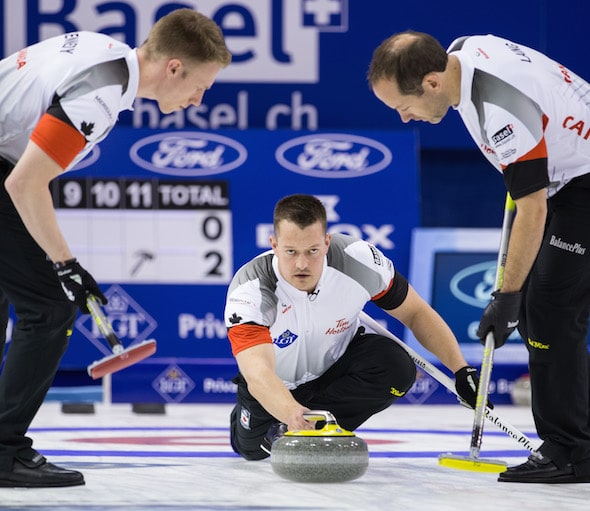 Team Canada lead Ben Hebert delivers rock to sweepers Marc Kennedy, left, and Brent Laing. (Photo, World Curling Federation/Céline Stuckli)
