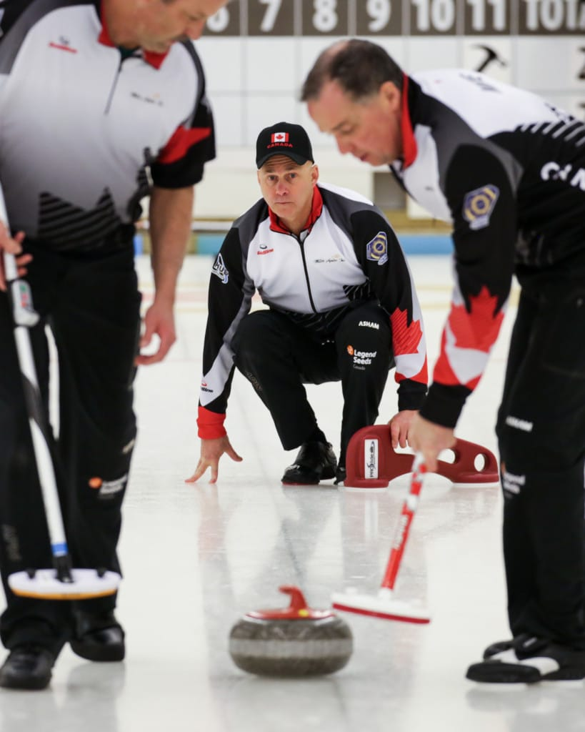 Canadian skip Randy Neufeld watches his rock as sweepers Peter Nicholls, left, and Dale Michie keep an eye on the weight during Saturday's 8-2 victory over Slovakia. (Photo, World Curling Federation/Céline Stucki)