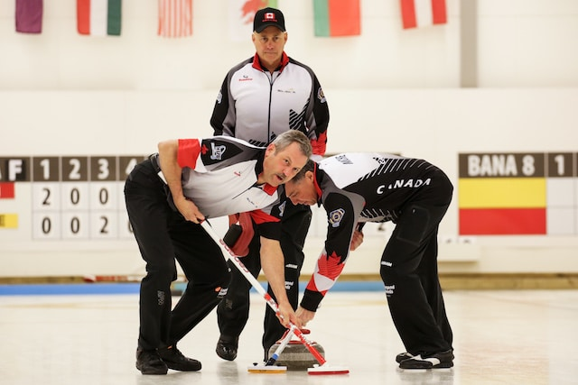 Dale Michie and Dean Moxham sweep skip Randy Neufeld's rock at the 2016 World Senior Men's Curling Champioships at the Karlstad Curling Arena (WCF/Céline Stucki photo)