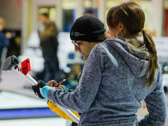 NRC's Louis Poirier (left) analyses data with curler Emma Miskew. (Photo, National Research Council/Dan Gamache)