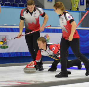 Team Canada skip Mick Lizmore delivers his rock, closely watched by second Brad Thiessen and lead Alison Kotylak during action at the Kazan Sport Palace during the 2016 World Mixed Curling Championship (Photo World Curling Federation/Alina Androsova)
