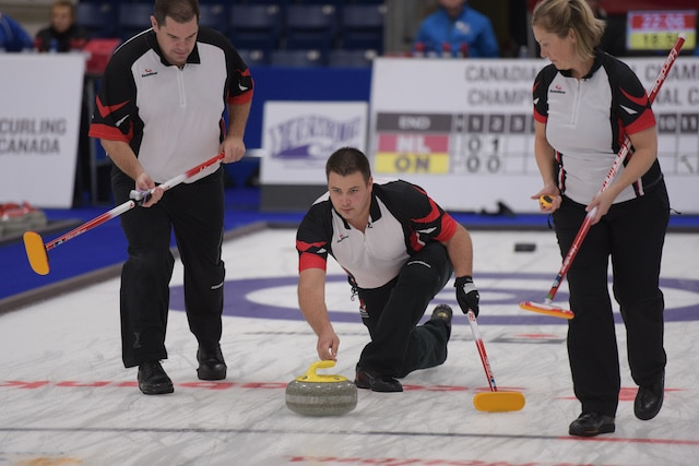 Ontario skip Wayne Tuck delivers his rock as second Jack Higgs and lead Sara Gatchell get ready to sweep at the 2017 Canadian Mixed Curling Championship (Curling Canada photo)
