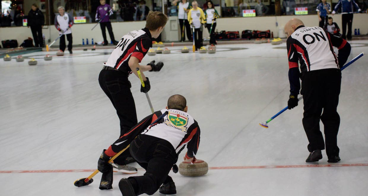 Ontario skip Wesley Forget delivers his rock at the 2016 Travelers Curling Club Championship in Kelowna, B.C., as second Graham Rathwell and lead Sandy Staples prepare to sweep (Curling Canada/Jessica Krebs photo)