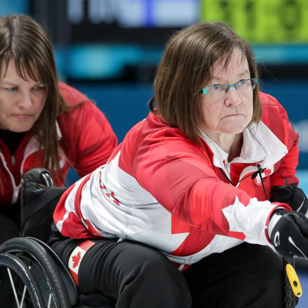 Ina Forrest hold the chair for Marie Wright as she delivers at the 29018 Paralympic Winter Games PyeongChang 2018.