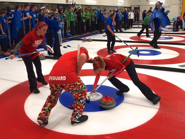 Red Team sweep their rock towards the button during the shoot out competition. (Photo by Lisa Shamchuk)
