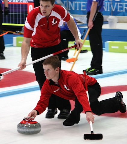 Team Canada third Michael Lizmore slides out as second Brad Thiessen prepares to sweep during Sunday morning action at the 2013 Winter Universiade in Trentino, Italy (Photo courtesy L. Thiessen)