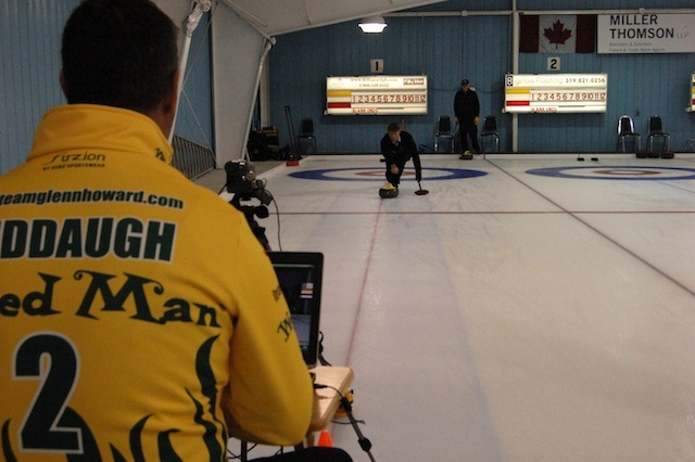 Wayne Middaugh runs the video equipment as curler Skid Crease tries to keep the laser's red dot in the middle of his rock (Photo Jean Mills)