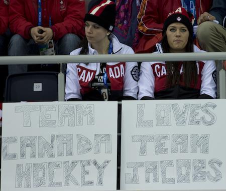 Shannon Szabados, left, and Natalie Spooner of the Canadian women 's hockey team cheer on Team Brad Jacobs on Thursday. (Photo, CCA/Michael Burns)