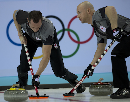 Team Canada's E.J. Harnden, left, and Ryan Fry sweep a rock during Wednesday's semifinal.