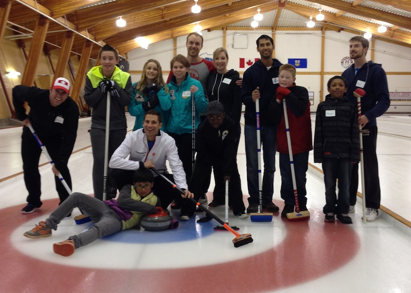 Little and Big Brothers and Sisters have fun with curler John Morris on the ice at the North Hill Curling Club in Calgary (Photo courtesy BBBS Calgary)