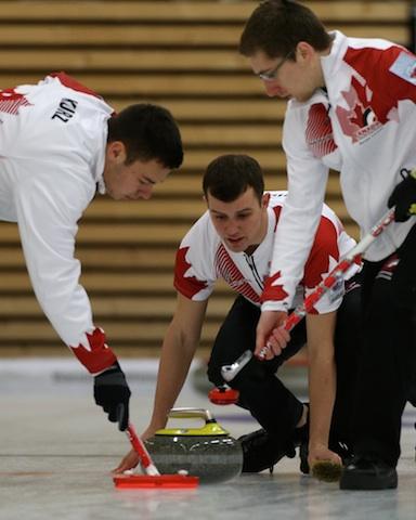 Kyle Kurz, Brendan Wilson and Lucas Van Den Bosch in action during the Bronze Medal game at the 2014 World Junior Curling Championships in Flims, Switzerland (Photo WCF/Richard Gray)