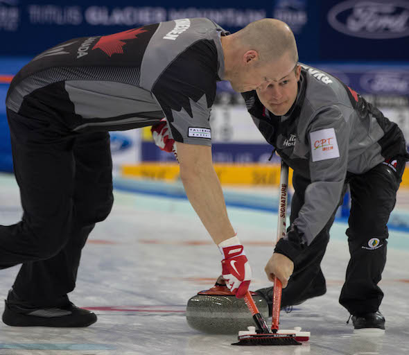 Team Canada's Nolan Thiessen, left, and Carter Rycroft go to work during win over Russia on Monday.  (Photo, World Curling Federation/Richard Gray)