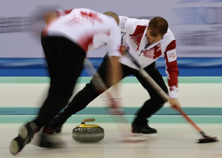 Team Canada sweepers Nolan Thiessen, left, and Carter Rycroft work on a rock during the bronze-medal game. (Photo, World Curling Federation / Richard Gray)