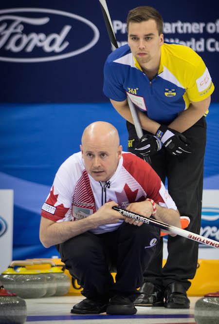 Team Canada skip Kevin Koe watches a shot as Swedish skip Oskar Eriksson looks on.  (Photo, World Curling Federation / Céline Stucki)