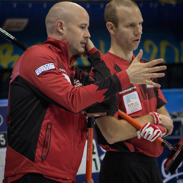 Team Canada skip Kevin Koe, left, and vice-skip Pat Simmons discuss strategy during Tuesday's win over the United States. (Photo, World Curling Federation / Céline Stucki)