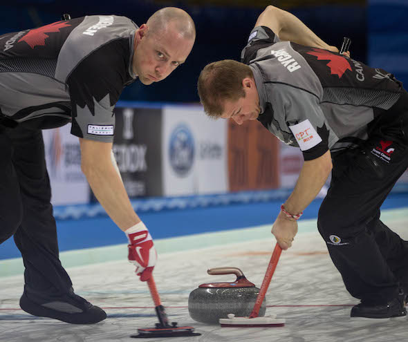Team Canada sweepers Nolan Thiessen, left, and Carter Rycroft were working hard on Wednesday. (Photo, World Curling Federation / Céline Stucki)