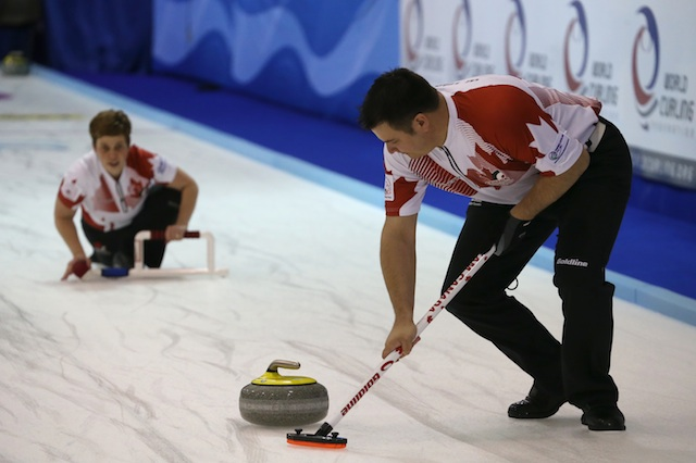 Team Canada's Wayne Tuck sweeps as Kim Tuck delivers her rock at the 2014 World Mixed Doubles Curling Championship in Dumfries, Scotland (Photo WCF/Richard Gray)