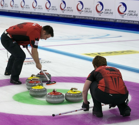 Wayne Tuck sweeps a rock into the house as Kim Tuck calls the line at the 2014 World Mixed Doubles Curling Championship in Dumfries, Scotland (Photo WCF/Richard Gray)