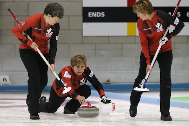 Colleen Pinkney delivers to sweepers Susan Creelman and Shelley MacNutt during playoff action at the 2014 World Senior Curling Championship in Dumfries, Scotland (Photo WCF/Richard Gray)