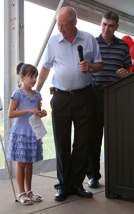 Junior curler essay winner eight-year-old Riley Puhl, left, is joined on stage by her grandfather Norman Todd, middle, and Greg Stremlaw, Chief Executive Officer of the Canadian Curling Association. (Photo, CCA/Neil Valois)